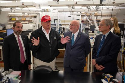 President Donald Trump speaks as Health and Human Service Secretary Alex Azar, left, CDC Director Robert Redfield and CDC Associate Director for Laboratory Science and Safety Dr. Steve Monroe, right,look on during a tour of the Centers for Disease Control and Prevention in Atlanta earlier this month to talk about the coronavirus.