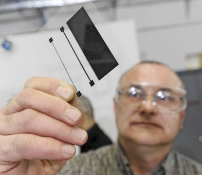 Dan Scheffer, director of research and development, holds up a test screen print made with graphene.
