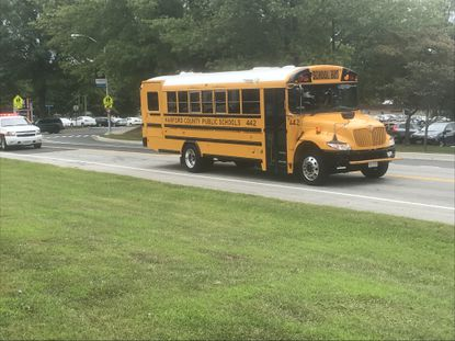 Local law enforcement officers will be riding school buses periodically this year in an effort to cut down on the number of drivers passing the bus when its red lights are flashing.