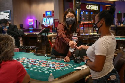 Table games dealer SoonChon offers a guest a spritz of hand sanitizer upon her arrival to the roulette table during the Horseshoe Casino's reopening Friday for its rewards members.