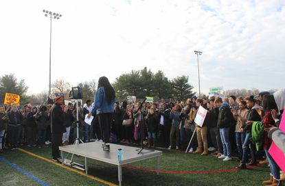 Nearly 400 students at Oakland Mills High School walked out of their classes and into the school stadium for about an hour Wednesday morning to support a change in school system policy some said would enhance communication of racial threats between the administration and community.