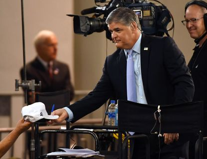 In this file photo, Fox News Channel and radio talk show host Sean Hannity autographs a Trump hat for an attendee before a Donald Trump campaign rally at the Las Vegas Convention Center in 2018 in Las Vegas, NV. Hannity has been at Fox News since it first launched in 1996. But it's only recently that he's become the network's biggest star, outlasting its first breakout host, Bill O'Reilly.
