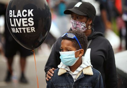 Tiffany Merrills and her son Aiden, 9, listen to speakers as the Chicago Chapter of Jack and Jill holds a non-violent march against racism for kids and families down Drexel Boulevard in the Bronzeville neighborhood Saturday, June 13, 2020. (E. Jason Wambsgans/Chicago Tribune)