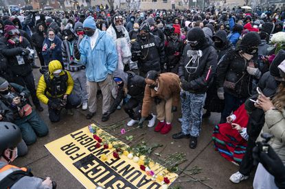Flowers are placed on a banner as demonstrators gather outside the Brooklyn Center Police Department on Tuesday, April 13, 2021, to protest the shooting death of Daunte Wright on Sunday during a traffic stop in Brooklyn Center, Minnesota. (AP Photo/John Minchillo)
