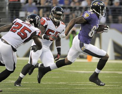 Ravens wide receiver Torrey Smith splits Atlanta safety William Moore and linebacker Joplo Bartu on his way to a touchdown in their preseason game last August.