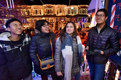 Foreign exchange high school students, from left, Adit Pradnyana of Bali, Ranim Yakoubi of Tunisia, Silvia Scata of Italy and Muhammad Ahmad Sohail of Pakistan experience the Miracle on 34th Street in Hampden. Dec. 19, 2019.