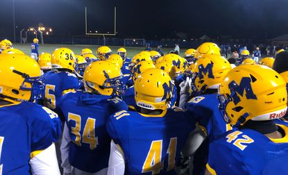 Mervo's football team huddles together during its playoff game against Towson on Friday, Nov. 15.