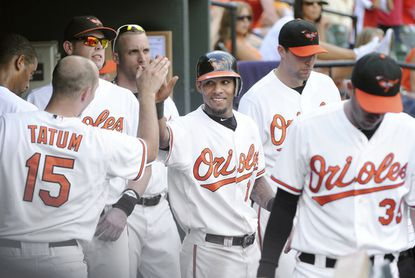 The Orioles' Robert Andino receives congratulations in the team's dugout after hitting a three-run homer to give the Orioles the lead in the fifth inning.