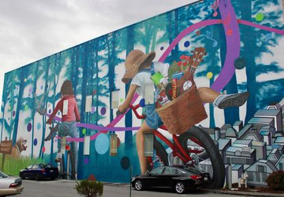 """""""Forward,"""" a new installation on the Catonsville Cube on Frederick Road, was painted by Baltimore-based artist Nether. A ribbon-cutting for the mural was held Dec. 7 near the Cube building at 757 Frederick Road."""