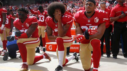 In this photo from Oct. 2, 2016, San Francisco 49ers' Eli Harold (58), quarterback Colin Kaepernick (7) and Eric Reid (35) kneel during the national anthem before their NFL game against the Dallas Cowboys in Santa Clara, Calif.