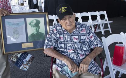 U.S. Army veteran Lambert Wai, 99, sits next to a picture of his brother Francis Wai, the only soldier of Chinese ancestry to receive the Congressional Medal of Honor, aboard the USS Missouri, during the official ceremony for the 75th anniversary of the Japanese surrender that ended World War II in Honolulu, on Wednesday, Sept. 2, 2020. (Craig T. Kojima/Honolulu Star-Advertiser via AP, Pool)