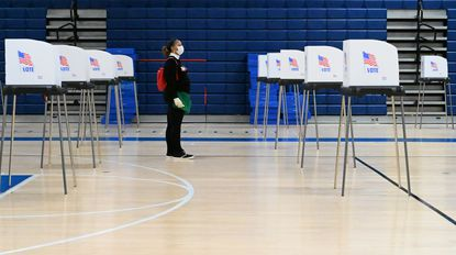 A volunteer waits to sanitize a booth during a lull at the voting location inside Howard High School on Election Day, Tuesday, Nov. 3.