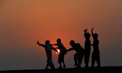 Pakistani children play on the roof of a house on the outskirts of Lahore on November 19, 2014. The United Nations' Universal Children's Day is celebrated annually on November 20 to promote worldwide fraternity and understanding between children.