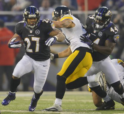 Baltimore Ravens running back Ray Rice runs past the block of teammate Vonta Leach (44) during the first half of their game in Baltimore.