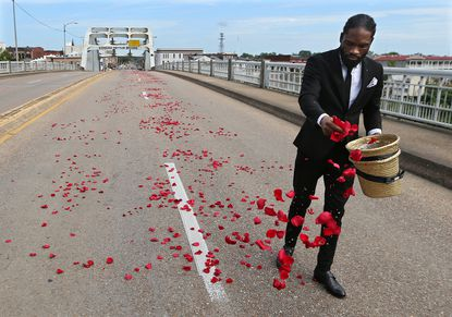 Justin Mayes spreads rose petals, representing blood shed on the Edmund Pettus Bridge, for the final crossing of Rep. John Lewis over the bridge, site of the historic 1965 voting rights marches, on Sunday, July 26, 2020 in Selma, Alabama. The congressman from Georgia and civil rights icon died July 17 at age 80 after a battle with pancreatic cancer.