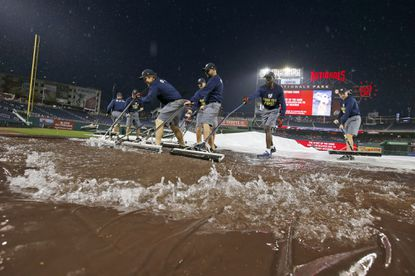 Members of the grounds crew squeegee rainwater off the tarp the Washington Nationals and the Orioles were rained out at Nationals Park, Monday, Sept. 21, 2015, in Washington.