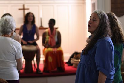 Eileen Carson, director of Footworks, sings along with the Ubuntu Community Choir during a practice for a performance at Common Ground in Westminster Thursday, July 4.