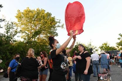 Capria Dawson 18, of Essex, releases wishing lantern during vigil for two children found dead in trunk of car during a routine traffic stop.