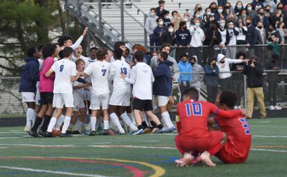 A pair of Centennial teammates console each other as Marriotts Ridge teammates celebrate their 1-0 win during the boys soccer county championship game at Wilde Lake High School on April 16.