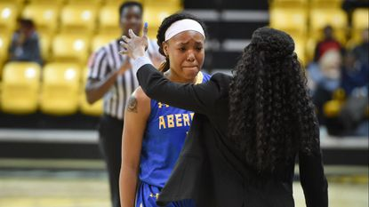 Aberdeen's Jaelyne Deveaux fights back the tears as she comes off and is greeted by Head Coach Jimmia McCluskey after fouling out of Thursday night's 3A state semifinal game against Baltimore Polytechnic at the SECU Arena at Towson University.