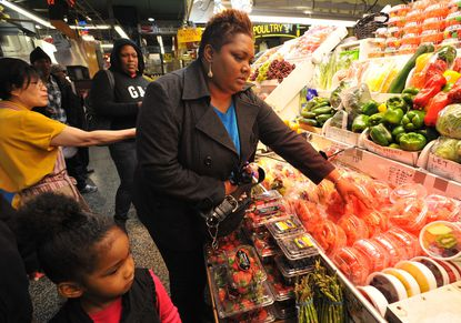 Sharon Franklin of Odenton, center, shopping with her granddaughter Sahmia Brown, lower left, opted for fruit and vegetables during a visit to Lexington Market.