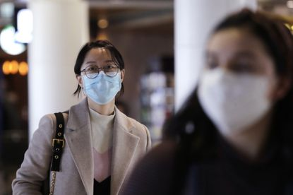 Travelers at Seattle-Tacoma International Airport wear masks Tuesday, March 3, 2020, in SeaTac, Wash. Six of the 18 Western Washington residents with the coronavirus have died as health officials rush to test more suspected cases and communities brace for spread of the disease. All confirmed cases of the virus in Washington are in Snohomish and King counties. (AP Photo/Elaine Thompson)