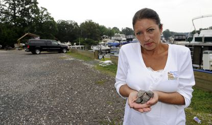 Nancy Correlli, one of the co-owners of Baltimore Boating Center, stands in the parking lot, which is made of loose stone. She is holding a handful of stones from the lot. Baltimore County says the parking lot is impervious and is therefore subject to a $4700 rain tax. The county had previously declared that the lot was porous.