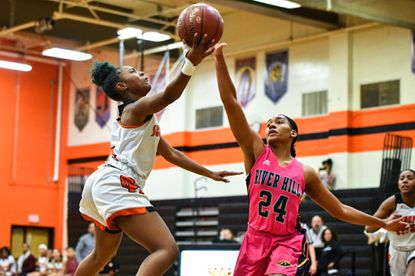 Oakland Mills Scorpions guard Jazmine Washington (4) goes to the basket and attempts a lay up over River Hill Hawks forward Saniha Jackson (24) during the first half at Oakland Mills High School.