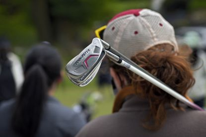 Ashley Cottrell of Canton holds chipper and wedge clubs to her shoulder while listening to instructions about chipping during the Fore the Ladies golf clinic at Forest Park Golf Course Sat., April 17, 2021. (Karl Merton Ferron/Baltimore Sun Staff)
