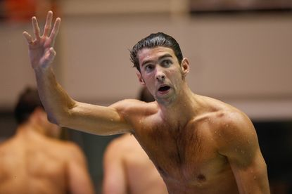 Michael Phelps waves to the crowd after winning the 100 Meter Butterfly during the finals of the AT&T Winter National Championships at the Weyerhaeuser King County Aquatic Center on December 4, 2015 in Federal Way, Washington.