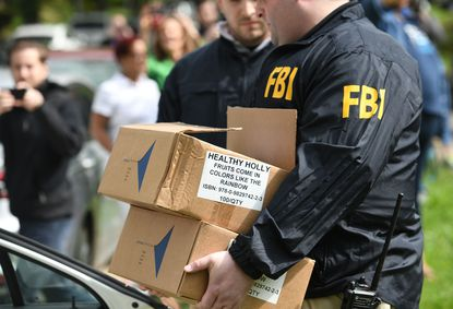 """Federal prosecutors laid out an array of new details from their investigation into former Baltimore Mayor Catherine E. Pugh in documents filed Thursday as they argued she should receive nearly five years in prison for conspiracy and tax evasion. In this 2019 photo, an FBI agent carries boxes of """"Healthy Holly"""" books out of Pugh's home."""