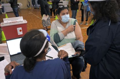 Lesbia Ruiz (center) asks to have her vaccination in her left arm, speaking to translator Maria Aponte while Theresa Williams, a registered nurse (left) listens during a coronavirus vaccination drive for the Hispanic population at Sacred Heart Church in Highlandtown, a vaccination site partnering with Johns Hopkins Hospital. March 24, 2021. (Karl Merton Ferron/Baltimore Sun).