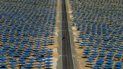 A car drives past some of the 347,000 garage door-sized mirrors awaiting the sun on opening day at the Ivanpah Solar Electric Generating System in the Ivanpah Valley near the California/Nevada border in 2014.