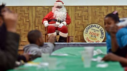 Santa Claus looks on as kids enjoy their meals during last year's Breakfast with Santa at the Independent Order of Odd Fellows Temple, in Towson.