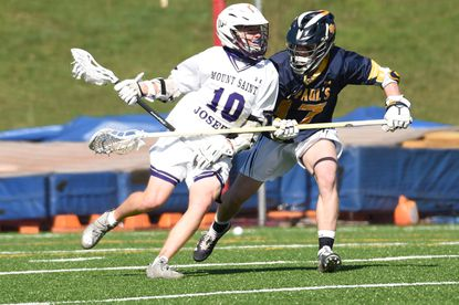 Mount St. Joseph's Alex Clyde, makes a move towards the goal, drawing pressure from St. Paul's Savon Thomas during a boys lacrosse game at Mount St. Joseph High School on Tuesday, March 30, 2021.