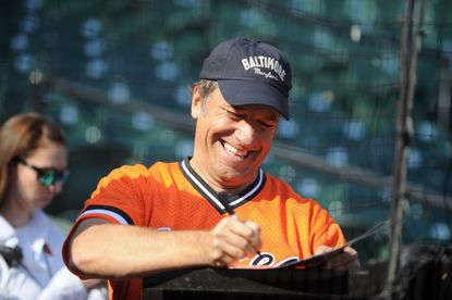"""Mike Rowe, host of CNN's """"Somebody's Gotta Do It,"""" signed autographs during pre-game activities before the Orioles played the Detroit Tigers in game two of the 2014 ALDS at Oriole Park at Camden Yards."""