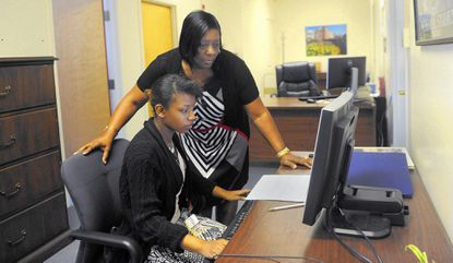 Nicola Paul, left, a 17 year old student at Atholton High School, works with her mentor and supervisor Denise Estep, right, who is the human resources administrator for the Maryland Department of General Services.