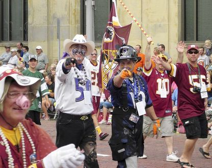 """Super fan Rick """"Poetic Justice"""" Bowlus, left, with Chip """" FIred Up"""" Riley in the 12th Man float in the Hall of Fame parade in Canton, Ohio."""