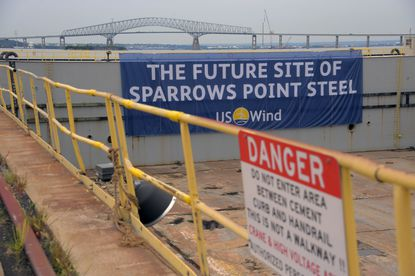 """The Francis Scott Key Bridge rises behind a banner tied onto a drydock which reads """"THE FUTURE SITE OF SPARROWS POINT STEEL"""" as US Wind and Tradepoint Atlantic announce a partnership agreement to lease 90 waterfront acres at the old Sparrows Point shipyard."""