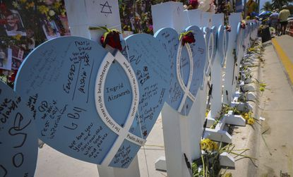 Wooden hearts with the names of Champlain Towers South victims are erected along with photos, flowers, and other memorial items. At least 90 people have been confirmed dead due to the partial collapse of the beachfront building. Sunday, July 11, 2021. (Carl Juste/Miami Herald via AP)