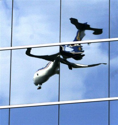 In this Sept. 3, 2007, file photo, a twisted reflection of a passenger jet is reflected in the mirrored windows of an office building as it lands at Washington's Reagan National Airport in Arlington, Va. The government wants to dramatically reduce the height limits of buildings near hundreds of airports, but the proposal is drawing fire from real estate developers, local business leaders and members of Congress who say it will reduce property values. (AP Photo/J. David Ake, File)