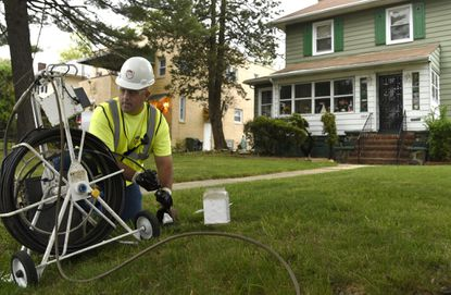 Field technician Jeff Howard uses a camera that can be snaked into drains to inspect sewer lines in the Ashburton neighborhood of West Baltimore.