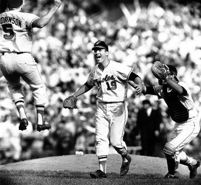 On Oct. 9, 1966 third baseman Brooks Robinson and catcher Andy Etchebarren converge on pitcher Dave McNally after the Orioles swept the Los Angeles Dodgers to win their first World Series.