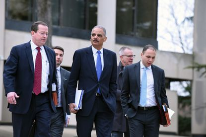 Former U.S. Attorney General Eric Holder, center, and associates leave the Maryland Court of Appeals after testifying before judges as they consider new rules aimed at reforming the state's cash bail system.