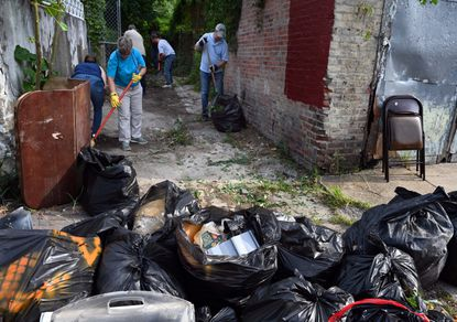 Volunteers clear an alley strewn with trash near Fulton Ave Monday morning. They were inspired to come out and help by Scott Presler, a Republican activist who organized the cleanup via Twitter.