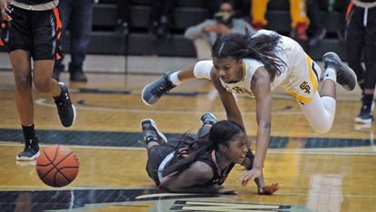 St. Frances' Nia Clouden, top, battles McDonogh's Treasure Valdez for the loose ball in the fourth quarter. The Panthers won the IAAM A championship game, 69-51, at Stevenson.