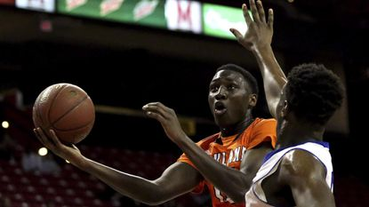 Mamadou Ndiaye, left, of Oakland Mills scores over Koran Moore of Patterson during the 2A State Basketball Championship game between Oakland Mills and Patterson at the Xfinity Center in College Park.
