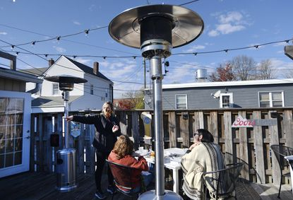 Kristy Harrison, a server and bartender at Rafael's in Westminster, helps diners in the restaurant's outdoor seating area which is outfitted with outdoor heaters as fall weather arrives Friday, Nov. 13, 2020.