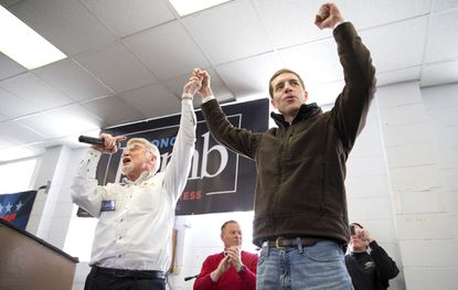 Cecil Roberts, left, president of the United Mine Workers, lifts up Democratic candidate Conor Lamb's hand as the crowd erupts in cheers and chants Sunday during a rally at the Greene County Fairgrounds in Waynesburg, Pa.