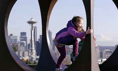Amazon is launching a travel service that will booktrips to Seattle, Los Angeles and New York, to start. Above, Emma Harrell, of Anchorage, Alaska, climbs inside a metal sculpture at the Space Needle and Mount Ranier in Seattle.
